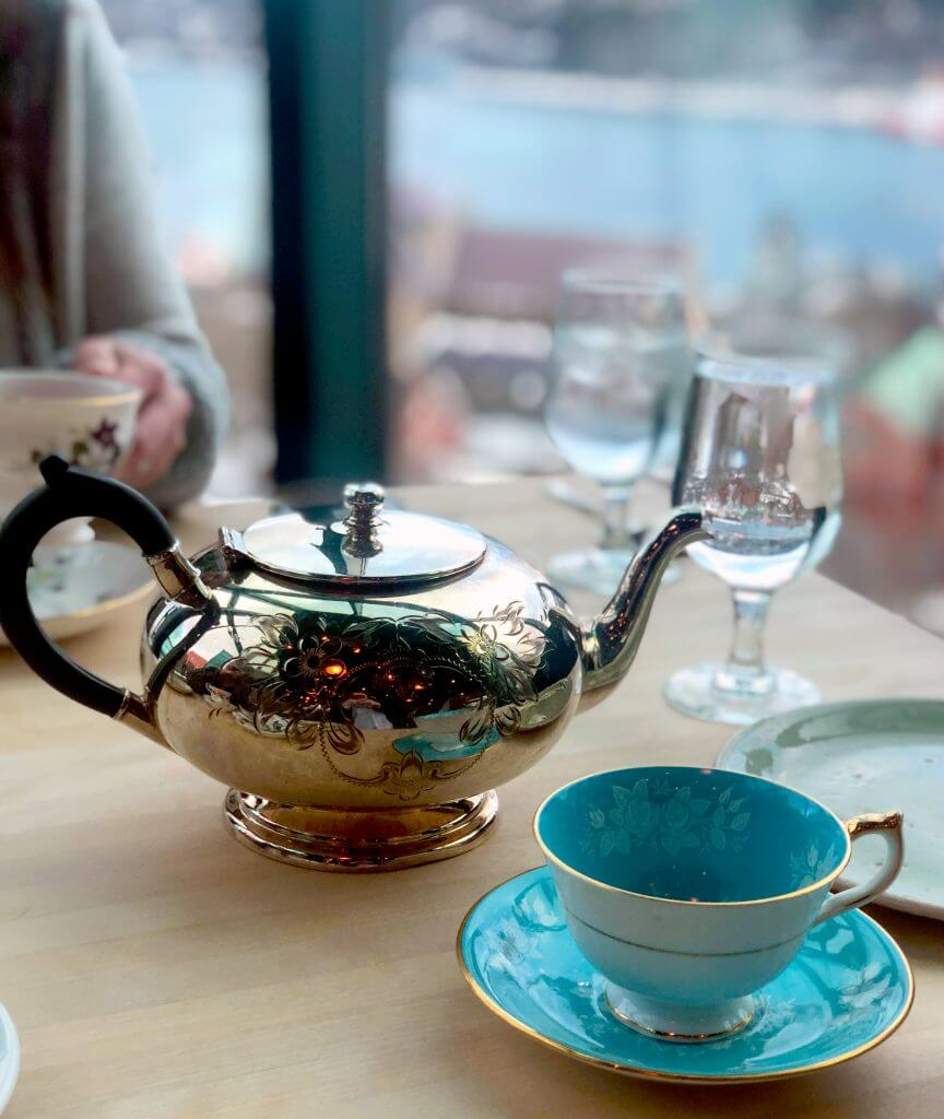 A close up shot of a silver tea pot next to a beautiful blue cup and saucer set with a light flower pattern and gold trim. In the background a guest holds a white tea cup.