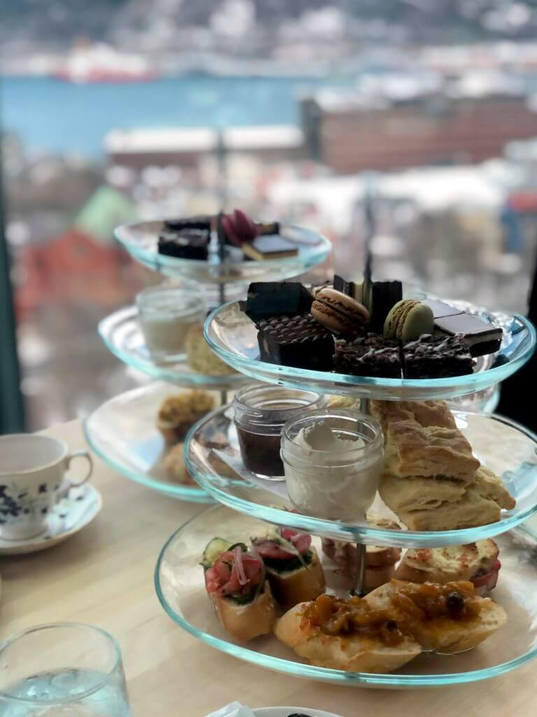 A three-tiered serving stand is given a close up. On top sits macarons, brownies, and other sweet treats.
