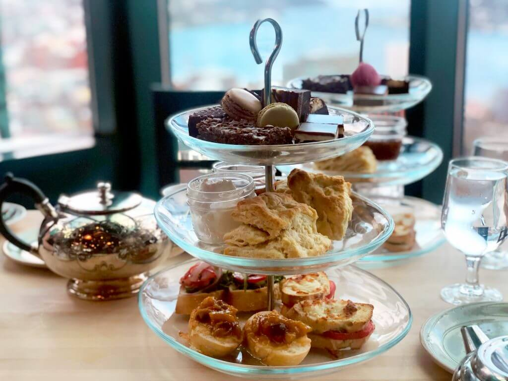 A three tiered serving stand holds sweets, sconess, and open-faced sandwiches. A second stand is in the background and a silver tea pot sits at the side.