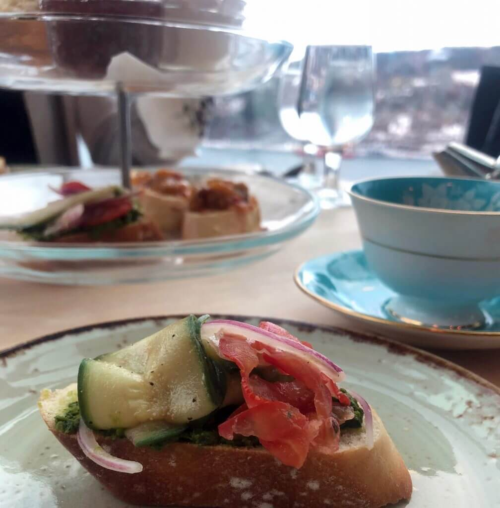 In the foreground, an open-faced vegetarian sandwich on a crostini. In the background there is a cup and saucer set as well as a serving stand full of treats.