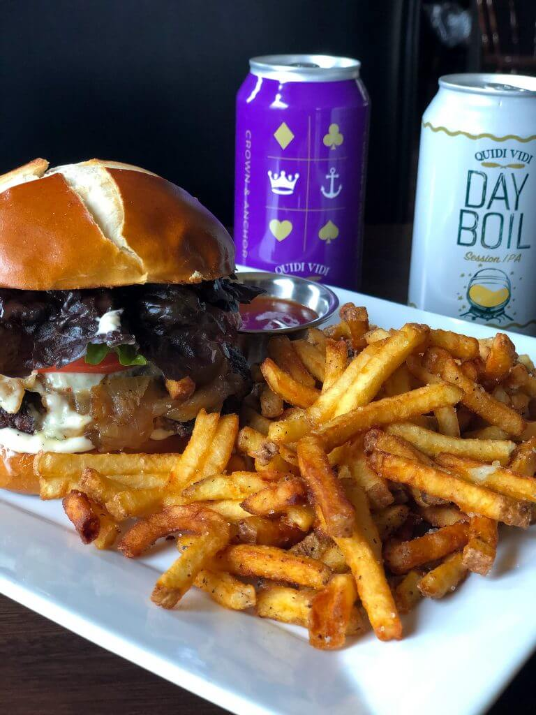 A burger and heaping serving of fries on a white plate with a can of Quidi Vidi Crown and Anchor and a can of Day Boil in the background.