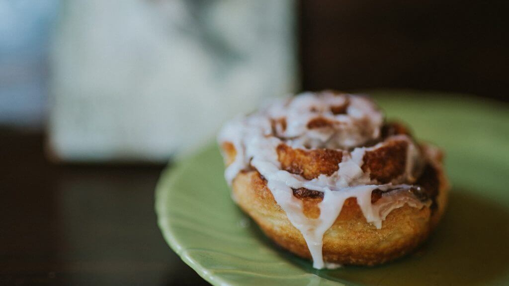 An up close shot of a cinnamon bun drizzled with icing sugar sitting on a green plate.