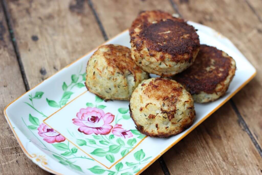 Four fishcakes on a white rectangular plate that has decorative pink flowers on it.