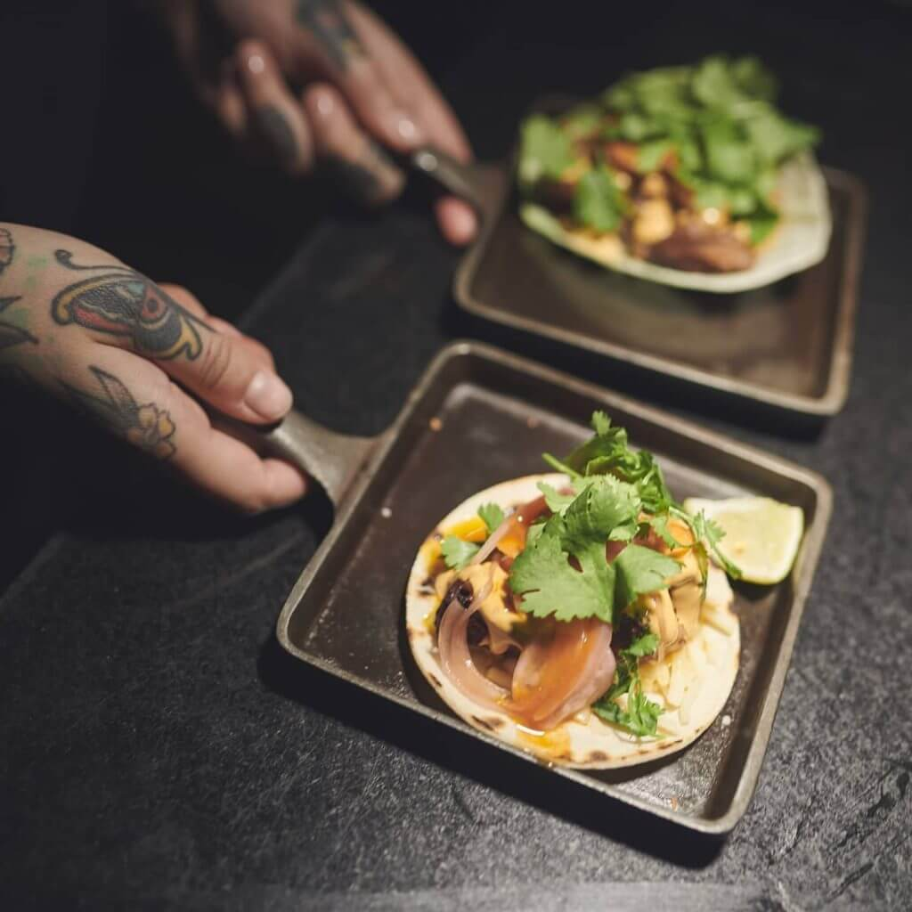 A team member holding two trays. Each is carrying a delicious looking taco.