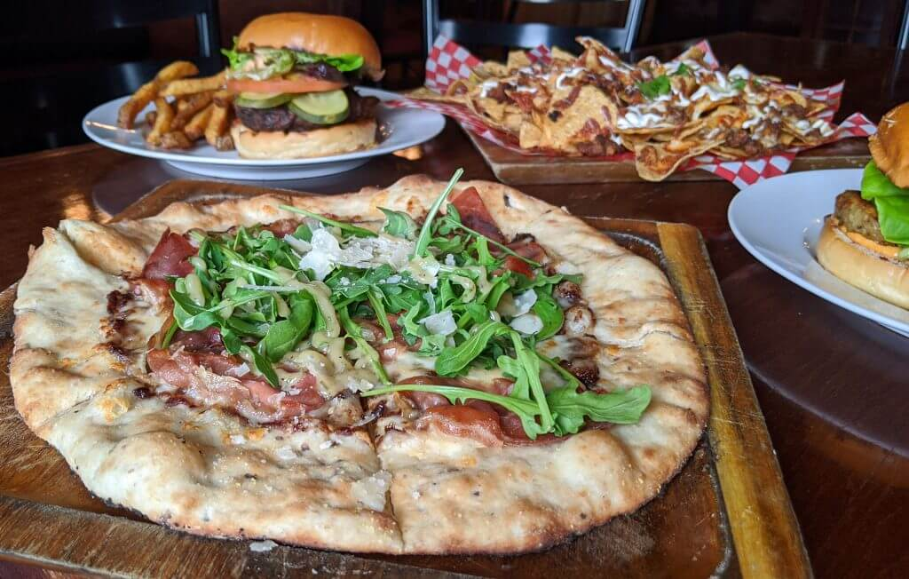 Wood-fired pizza that looks to be topped with arugula. A plate of nachos and a plate with a burger and fries in the background.