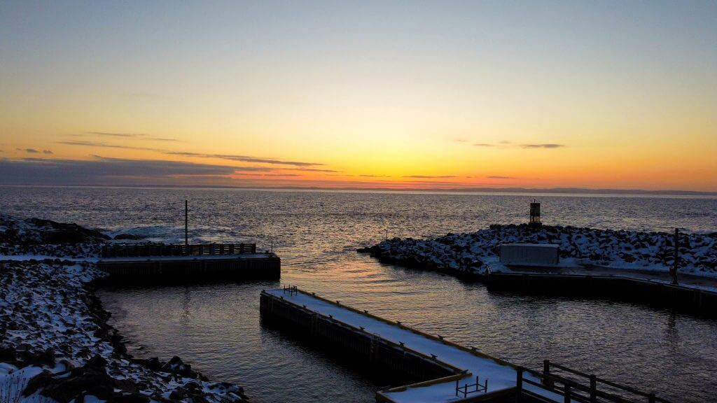 A sunset view from the wharf at Bauline overlooking the ocean. The wharf itself, and the ground, are covered with a dusting of snow.