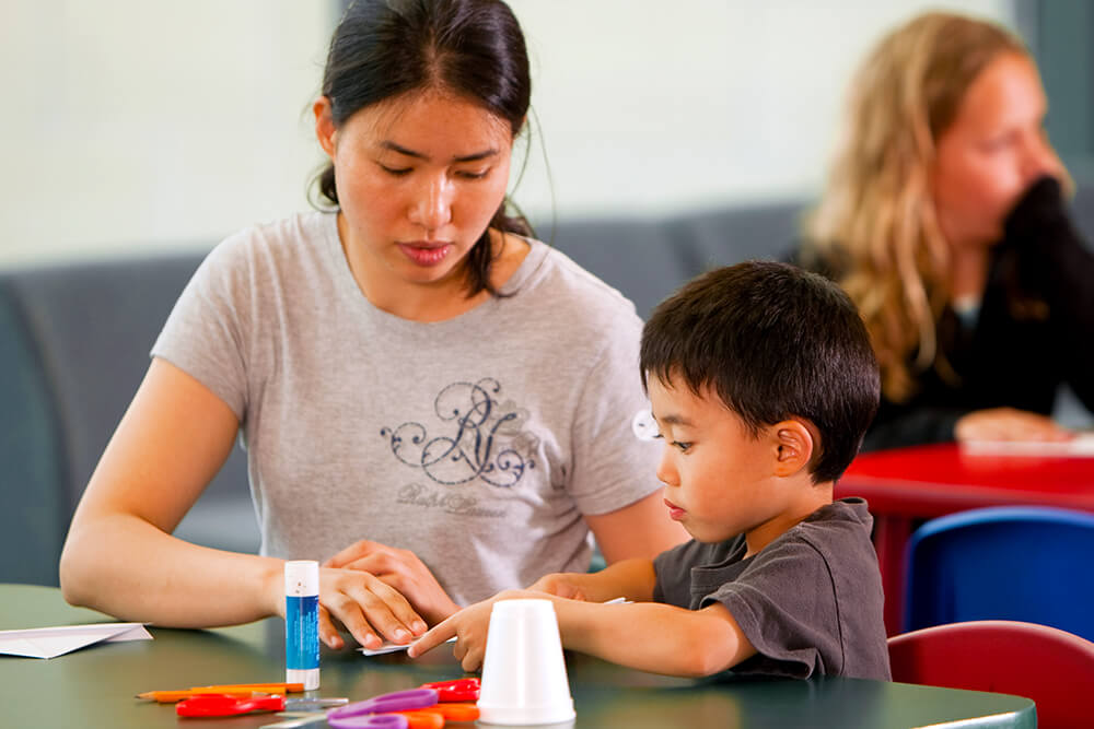 A mom and her young son are sitting at a table and working some crafts at The Rooms