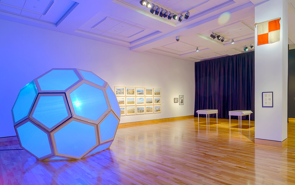 A large globe like piece of art resembling a soccer ball glows blue. It is sitting in a large open exhibit space with art hanging on a far wall.