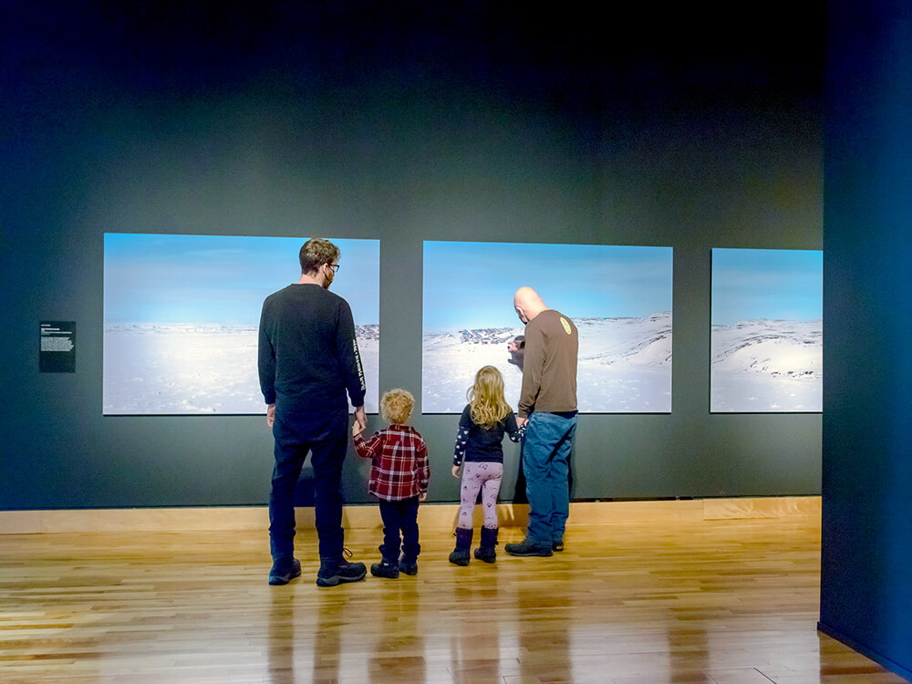 Two children holding their dads' hands as they look at art on a wall in The Rooms.