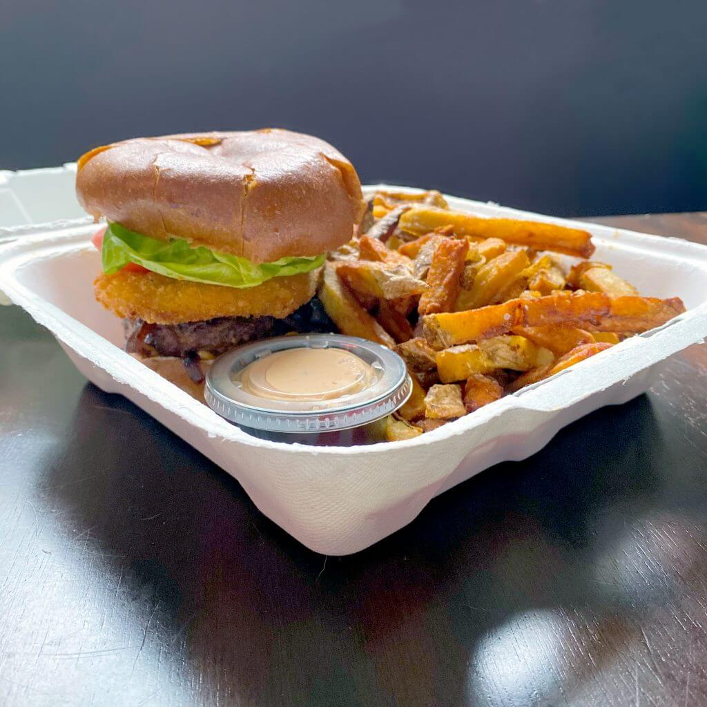 Yellowbelly Brewery burger and fries in a takeout container.