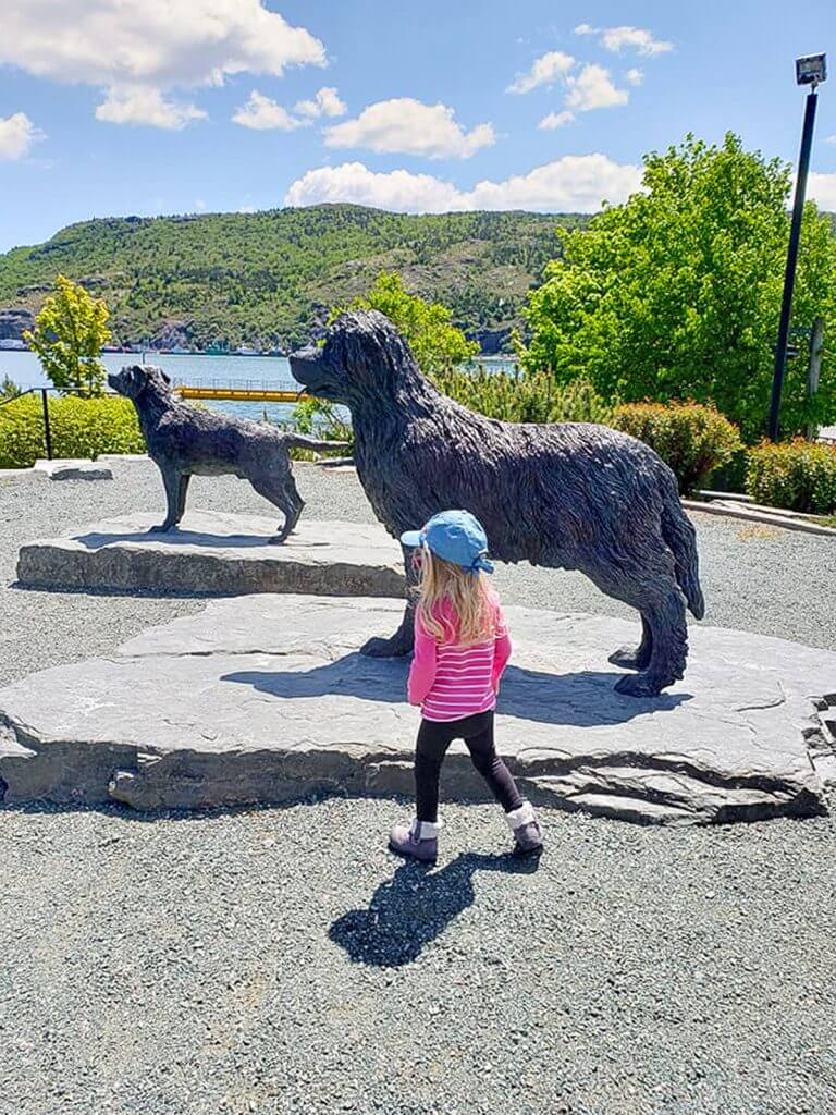 Blake walking through harbour side park right next to the two Newfoundland dogs. It's a beautiful sunny day.