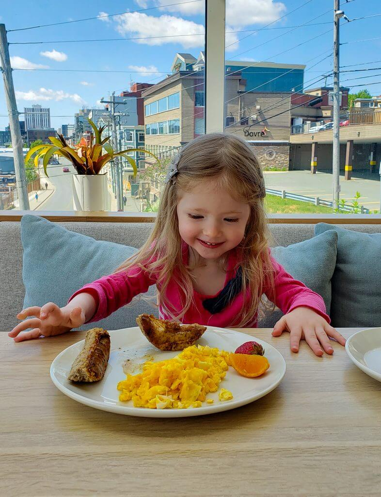 Blake with a big smile on her face looking lovingly at a plate of eggs, sausages, and fruit.